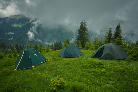 Camping and tents in the forest in the mountains, foggy weather 免版税图像