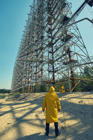 young man in yellow protective suit standing near military secret object antenna radar Duga in Chernobyl in Ukraine, place with higher radioactivity 版權商用圖片