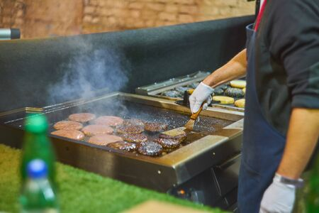 Make burgers on the grill restaurant. Burgers cooking on a gas grill in the evening sun Stock Photo