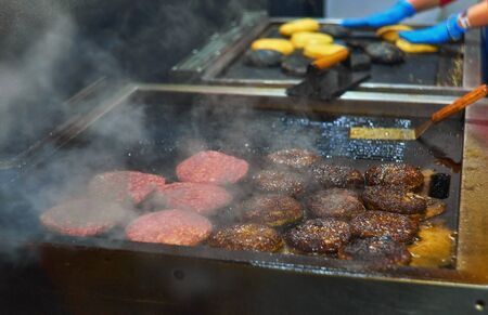 Make burgers on the grill restaurant. Burgers cooking on a gas grill in the evening sun Banco de Imagens