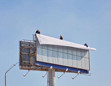 Worker prepares billboard to installing new advertisement. Industrial climber working on a ladder - placing an advertising banner.