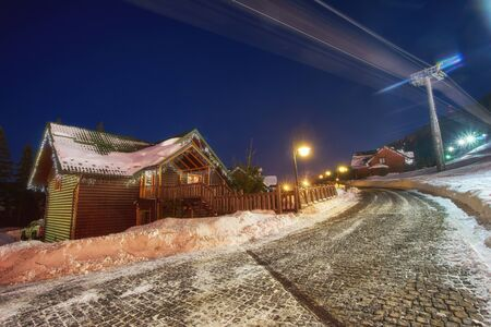 Ski resort in the style of an alpine village, cozy houses for rest in the winter at night