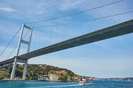Ships passing through Bosphorus Bridge with background of Bosphorus strait on a sunny day with background cloudy blue sky and blue sea in Istanbul, Turkey. Blue Turkey concept.