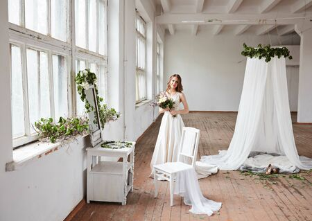 Belle mariée dans une robe de mariée dans un studio élégant et lumineux. Mariage à l'européenne. Décor et bouquet à la main. Jeune fille debout, assise et posant Banque d'images