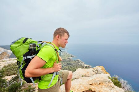 A tourist on a mountain with a backpack looks into the distance. Beautiful view of the sea bay