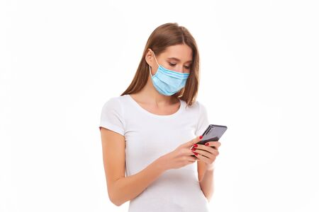 European Girl in a mask uses a telephone. Conceptual photo on the theme of the epidemic. Isolated on a white background.