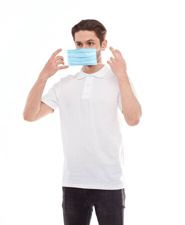 A man in a white T-shirt of European appearance puts on a medical mask. Isolated on a white background Reklamní fotografie