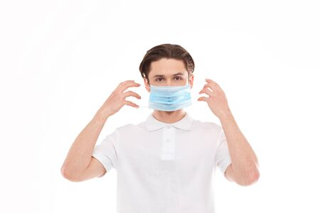A man in a white T-shirt of European appearance puts on a medical mask. Isolated on a white background