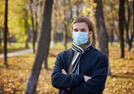 Portrait of young man with medical face mask stands at city street. Guy wearing protective mask from virus outdoor in the people crowdy. Concept of health and safety life from coronavirus pandemic. Stockfoto