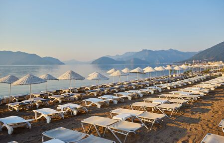 Deserted beach in the morning sun. The beach at dawn. Empty sunbeds. Beach without people. Marmaris, Turkey.