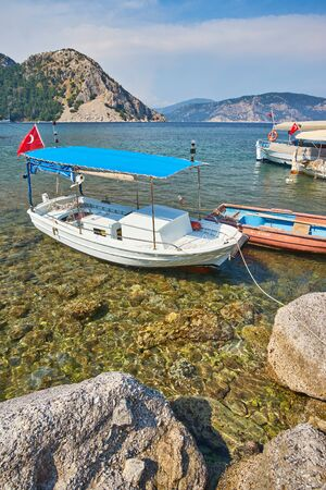 small boats moored in Aegean sea lagoon with mountainous islands around, beach at background and turkish flag at top of hill in Turunc, Mugla, Turkey Фото со стока
