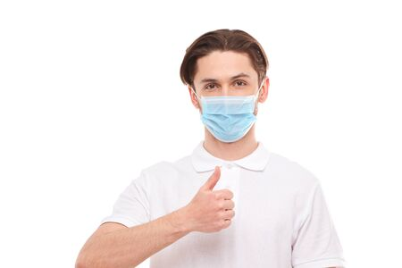 A man in a white T-shirt of European appearance in a medical mask, shows a thumb up. In the mask you are protected from covid 19 viruses. Isolated on white background Фото со стока