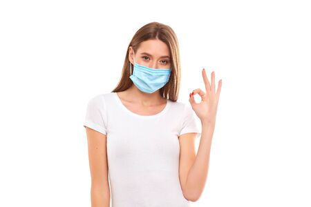 European girl in a medical mask, shows ok. Conceptual photo on the theme of the Covid 2019 pandemic. Isolated on a white background. Фото со стока