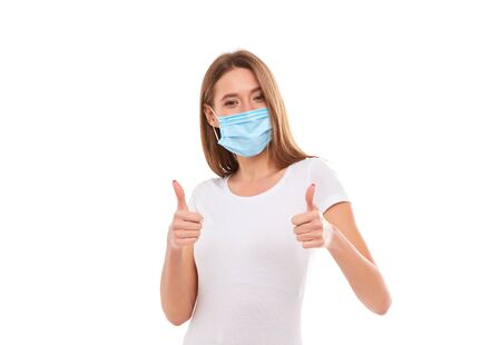 European girl in a medical mask, shows thumb up. Conceptual photo on the theme of the Covid 2019 pandemic. Isolated on a white background. Фото со стока