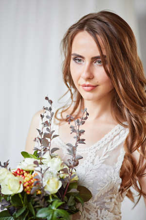 Beautiful bride in a wedding dress in a bright stylish Studio. Wedding in European style. Decor and bouquet in hand. Young girl standing, sitting and posing