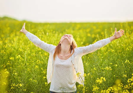 woman with open arms in the green rapeseed field at the morning.