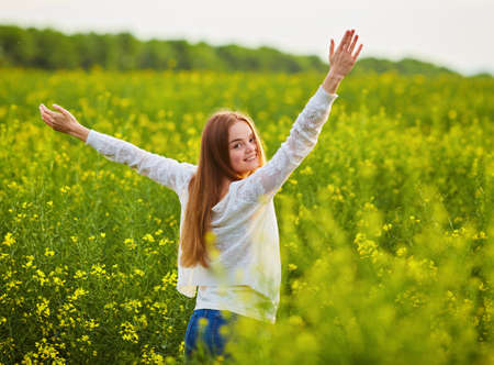 Redhead girl in a rapeseed field, on a sunny day