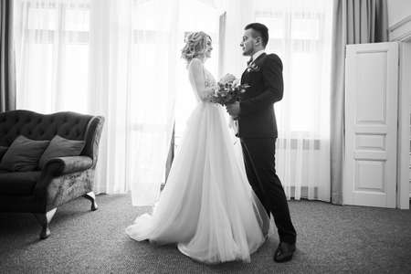 Black and white photo of happy newly married couple dancing