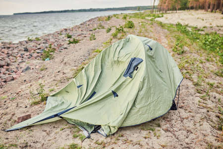 blue broken camping tent on the beach at the stormy weather and good tent at back 版權商用圖片