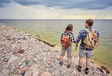Travelers couple look at the mountain lake. Travel and active life concept with team.