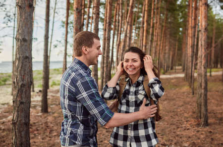 young couple smiling at each other during a romantic date in the forest - strong sunlight - shot against sun 版權商用圖片