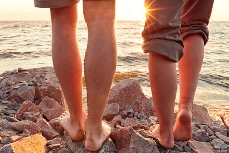 Legs on beach. Foot spa. A young loving couple hugging and kissing on the beach at sunset. Two lovers, man and woman barefoot near the water. Summer in love 版權商用圖片