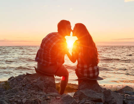 he and she on a nature outing. Romance and love.kiss in the sunset sun 版權商用圖片