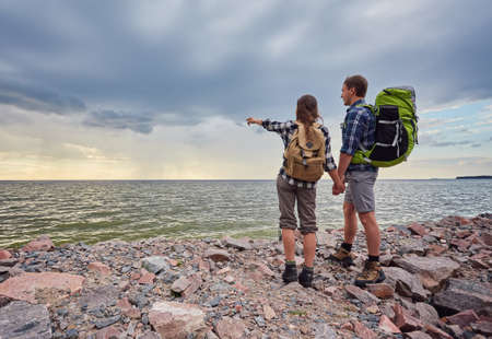 adventure, travel, tourism, hike and people concept - smiling couple with backpacks outdoors 版權商用圖片