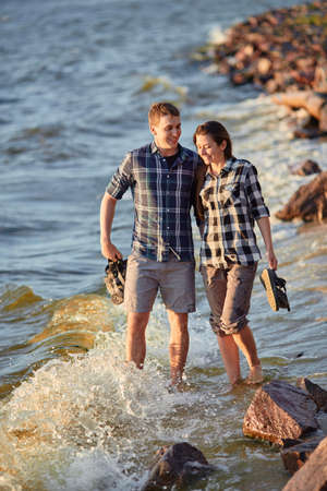 Happy caucasian fashionable couple in love holding hands and walking on coast near river. In background is sunset. 版權商用圖片