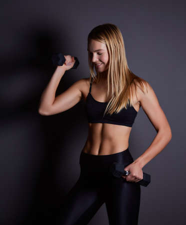 Young fitness blonde woman in the gym near the wall with dumbbells in her hands. 版權商用圖片