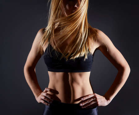 Sportive blonde girl on the background of the black wall of the gym. Body relief and hair sweep