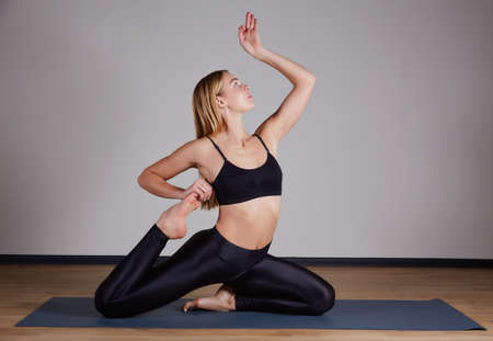 Young yogi woman practicing yoga concept, doing One Legged King Pigeon exercise, Eka Pada Rajakapotasana pose. Working out, wearing sportswear bra and pants, silhouette, loft studio background