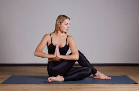 Young attractive woman practicing yoga, doing Half lord of the fishes exercise, Ardha Matsyendrasana pose with namaste. Working out, wearing sportswear, pants and top, indoor full length, yoga studio
