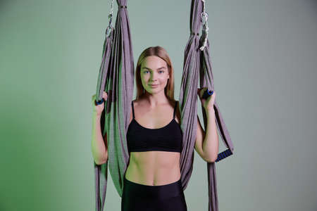 young woman making antigravity yoga exercises in modern gym
