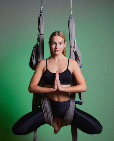 portrait young women making antigravity yoga exercises. Aerial aero fly fitness trainer workout. lotus. meditates. harmony and serenity concept