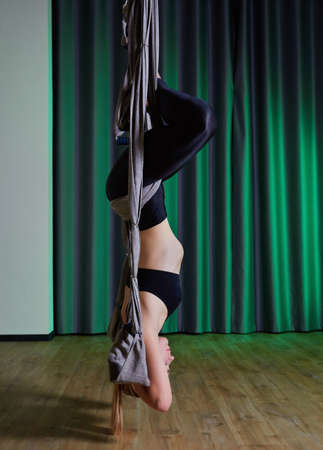 Attractive peaceful young woman doing aerial yoga in studio