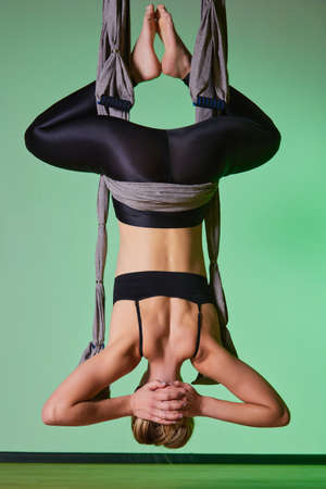 Back view of beautiful young woman using hammock for doing pose of antigravity yoga