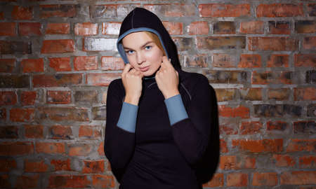 sport and yoga lifestyle concept. Young fit pretty woman dressed in sport clothes poses against brick wall.