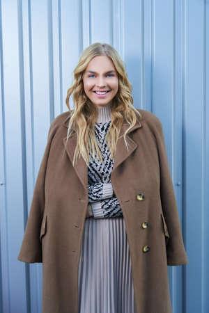 Stylish cute young blonde woman in seasonal fashionable beige coat posing near silver metal wall outdoors. Fashionable girl model in the city. 版權商用圖片