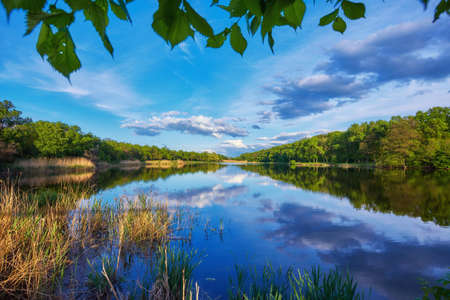 Beautiful river coast at sunset in summer. Colorful landscape with lake, green trees and grass, blue sky with multicolored clouds and orange sunlight reflected in water. Nature. Vibrant scenery 版權商用圖片