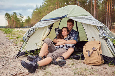 Romantic couple camping outdoors and sitting in a tent. Happy Man and woman on a romantic camping vacation. 版權商用圖片