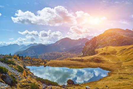 Overcast morning autumn alpine Dolomites mountain scene. Peaceful Valparola Path and Lake view, Belluno, Italy. Picturesque traveling, seasonal, and nature beauty concept scene. 版權商用圖片
