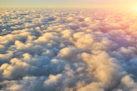 Spectacular view of a sunset above the clouds from airplane window