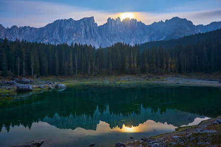 The Karersee lake or Lago di Carezza with reflection of mountains at night in the Dolomites, South Tyrol, Italy.