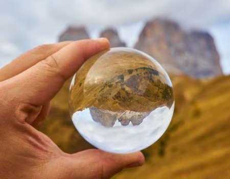 Alpine mountain view through crystal glass globe. Dolomites Alps, Italy