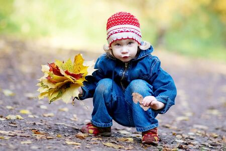 The girl with yellow leaves in autumn wood photo