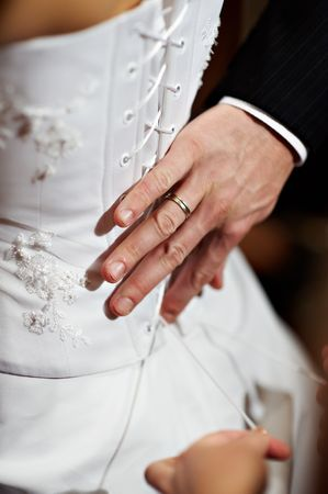 Hand the man with a ring on a finger at a dress of the bride photo