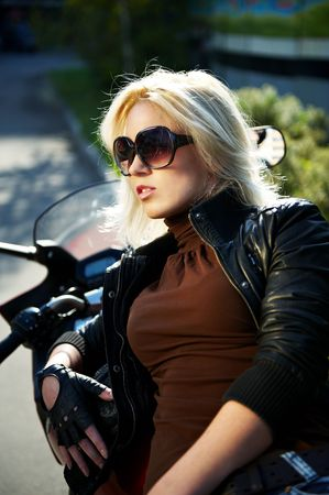 The girl the blonde in points at a stylish motorcycle photo
