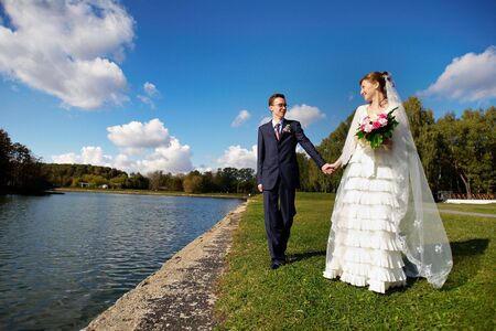 Bride and groom on wedding walk against a background of blue sky photo