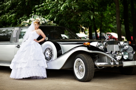 Luxury bride in a white wedding dress about big retro limousine